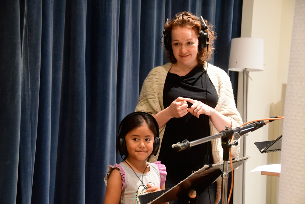 Vocal Coach Christine Brown helps an Olympic View student record her poem