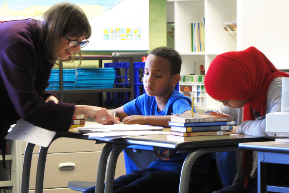 Poet Vicky Edmonds helps students write their poems at West Seattle Elementary