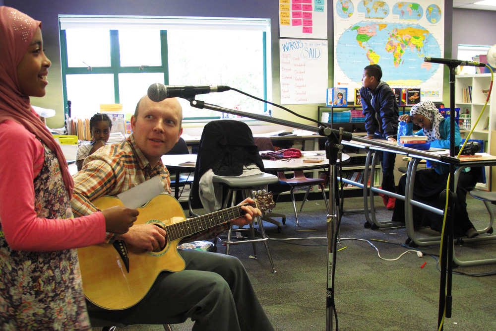 Levi Fuller plays guitar while a student practices vocalizing her poetry
