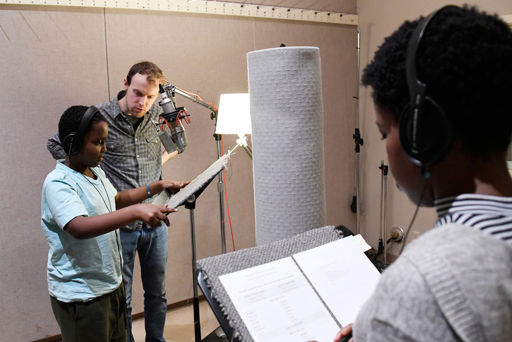 A student prepares to record his poem with Jack Straw engineer Daniel Guenther and vocal coach Claudine Mboligikpelani Nako