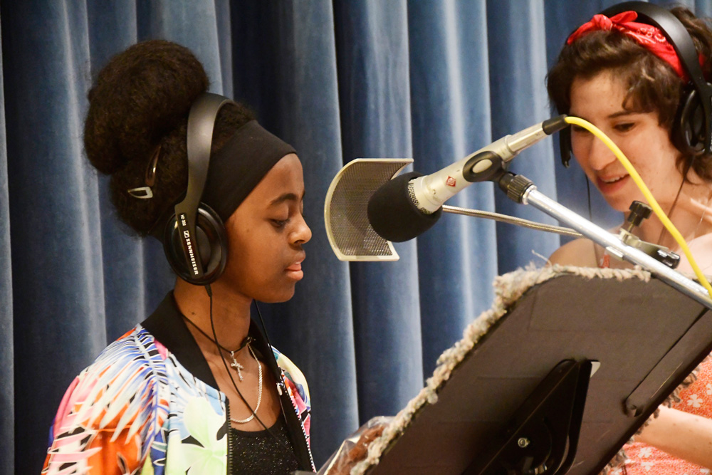 A World School student records her narration with the help of voice coach Katya Landau